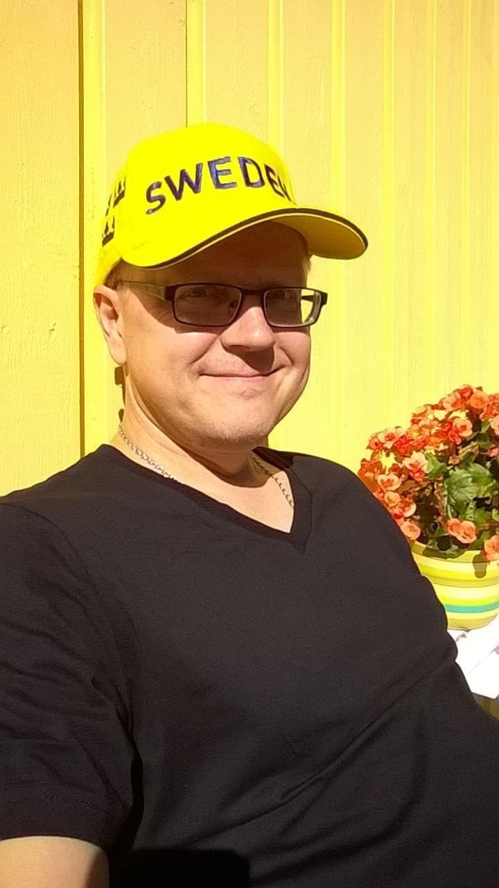"""Silmälasipäinen mies istuu päässään keltainen lippalakki, jossa lukee """"Sweden""""."""