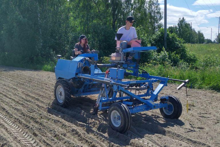 Kaksi opiskelijaa istuu sinisen koeruutujen kylvämiseen tarkoitetun koneen kyydissä pellolla.