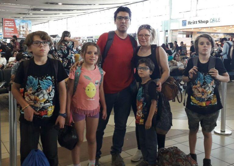 Kaksi aikuista ja neljä lasta seisovat lentokentän odotusaulassa matkatavaroiden kanssa.