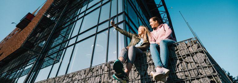Kaksi opiskelijaa istuu kivimuurin päällä./ Two students are sitting on a stone wall.
