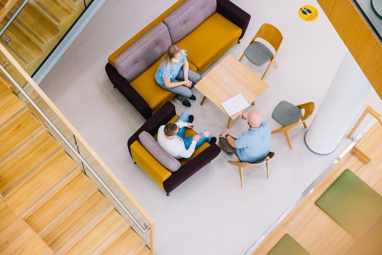 Ylhäältä kuvattu, kun opiskelijoita istuu pöytäryhmässä.