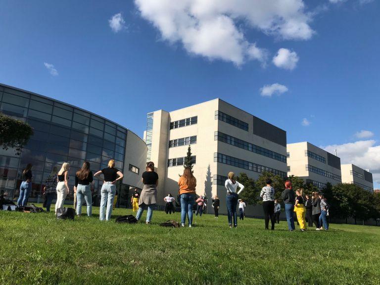 Opiskelijoita suuressa ringissä kampuksen nurmialueella.