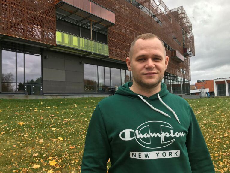 Nuori mies vihreässä hupparissa seisoo ulkona taustallaan yksi kampuksen rakennuksista.