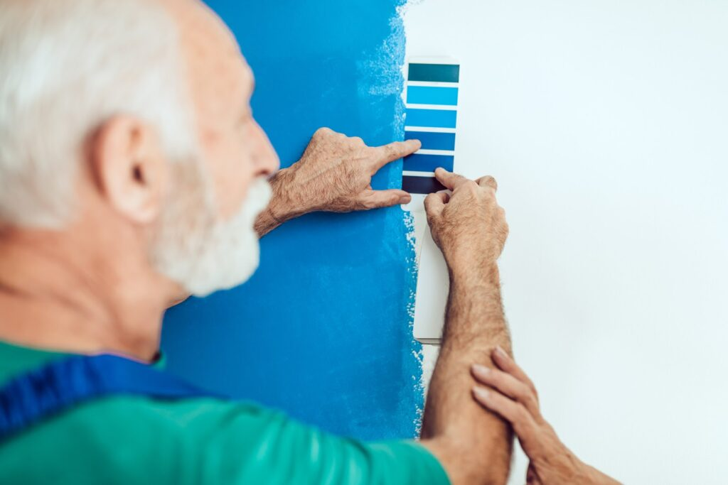 Senior male painter painting a wall