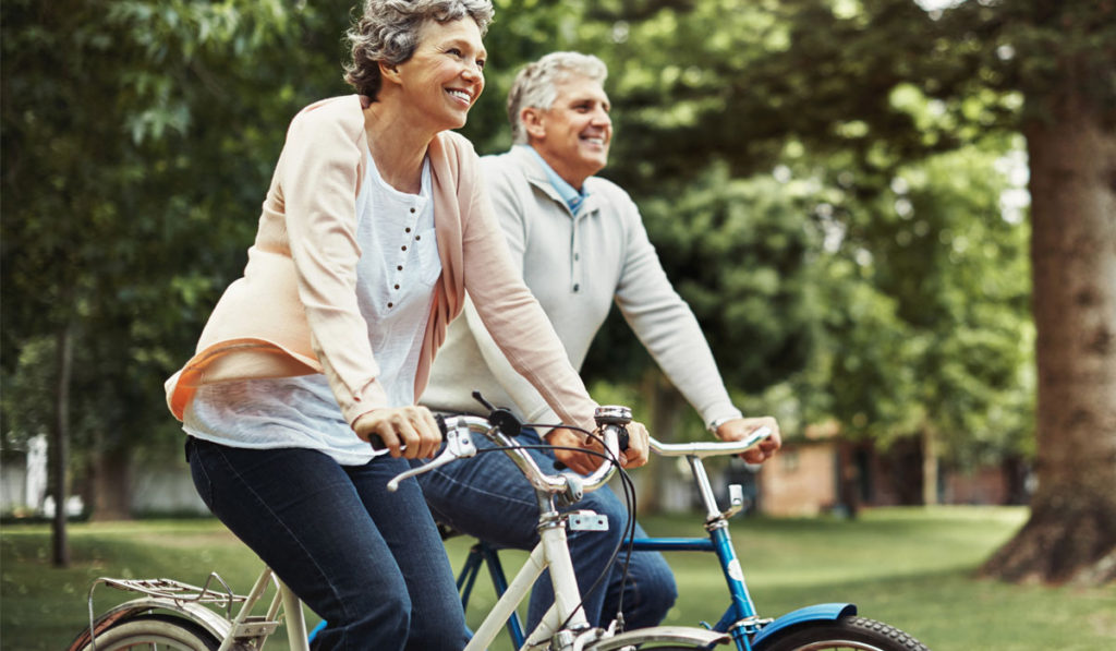 Sedgebrook resident couple biking outdoors by trees in a park