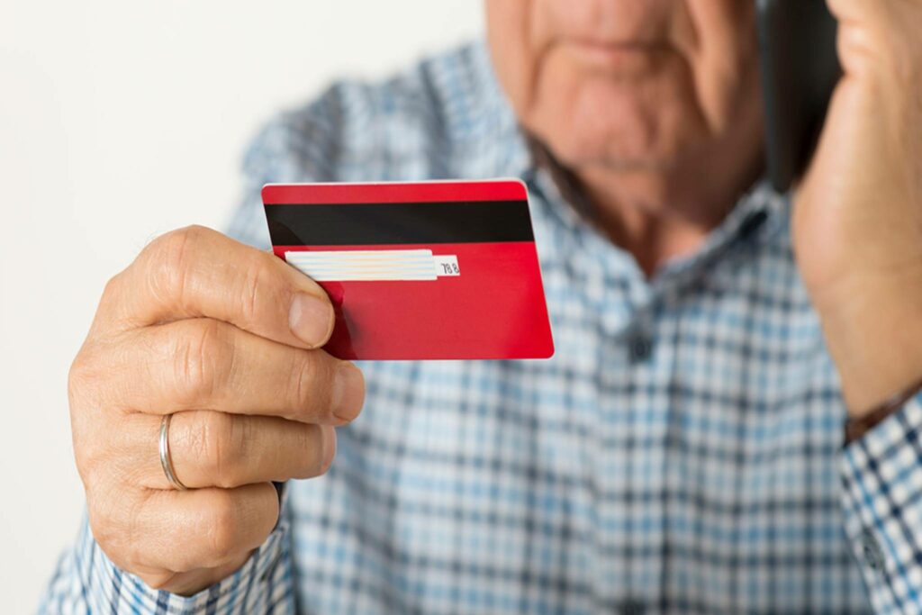 Senior man holding credit card and talking on the phone
