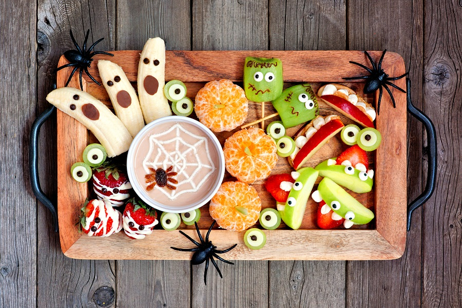 Tray of healthy Halloween fruit snacks top view over a rustic wood background