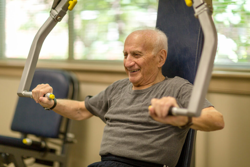 senior man does arm exercises in senior fitness center