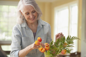 senior woman places flowers in a vase
