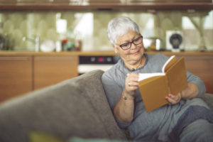 senior woman reads a book on her couch