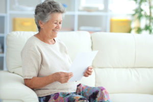 senior woman smiles at paper
