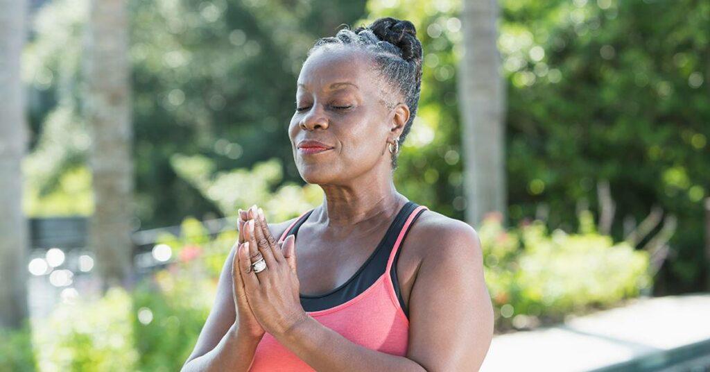 Senior woman meditating outside