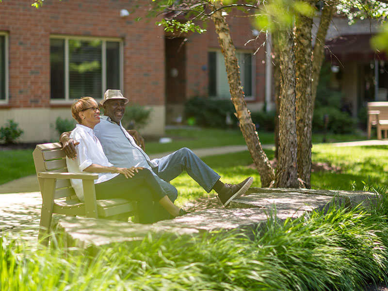 Senior couple sitting on bench at park at Sedgebrook senior living