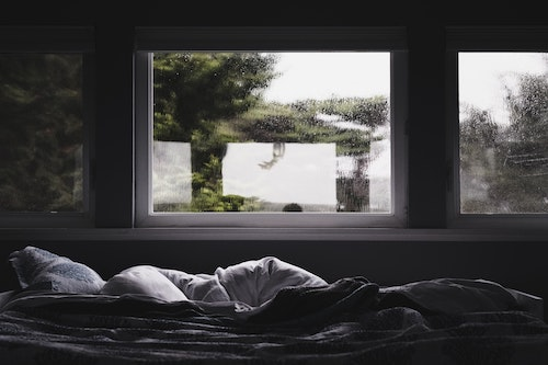 bed with white cushions in front of a rainy window