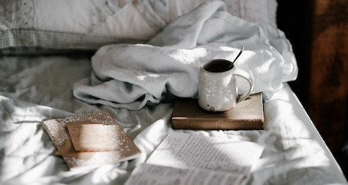 light brown books, a white mug and a scrunched up white blanket sit on top of a white quilt