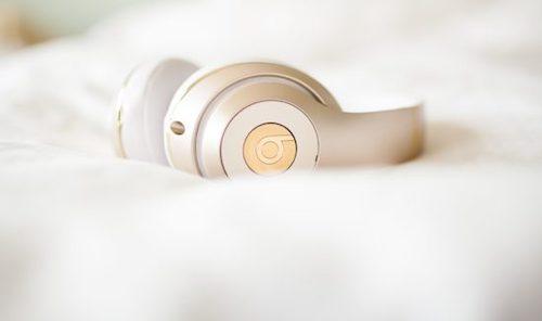 white headphones on a white bedsheet
