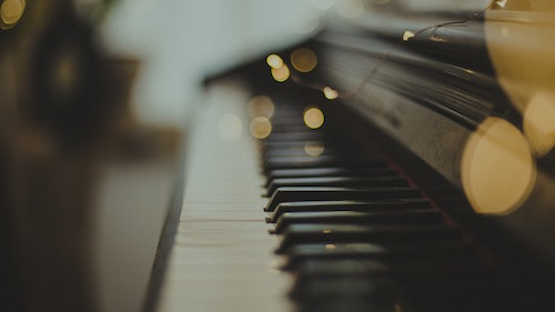 close up of a piano keyboard with fairy lights on top