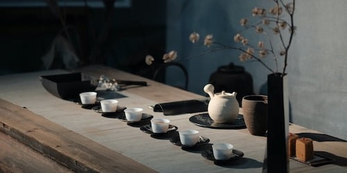 small white tea cups on a wooden table with a clay teapot and a black vase with white twiggy flowers in the foreground
