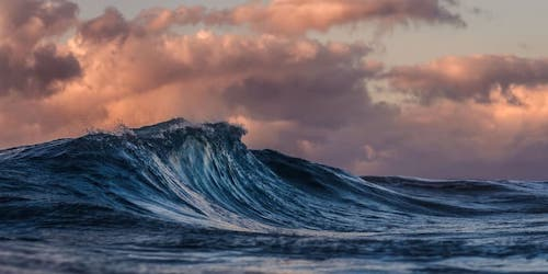 cresting ocean wave with pink clouds overhead