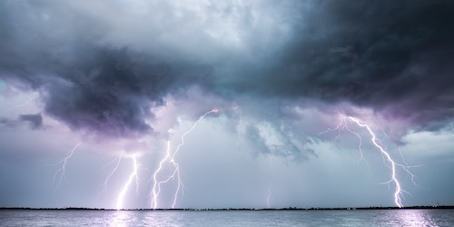 dark grey clouds with purple-hued lightning over the ocean