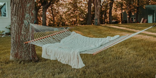 hammock with white blanket hanging from a tree over a lawn with trees and a sunset in the background