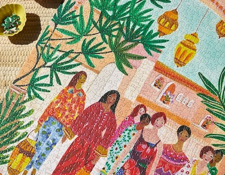 jigsaw puzzle of women in colourful dresses under green palm leaves