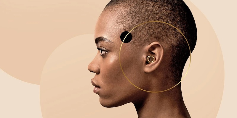 a Black woman with a shaved head wearing brass coloured Loop earplugs in front of beige coloured circles. A small black circle and a large gold circle are around her ear