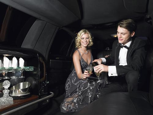 Ungt par med champagne i gallabil