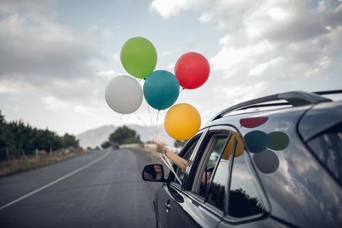Pige med balloner ud af bil