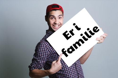 """Mand holder et kort op med teksten """"Er i familie"""""""