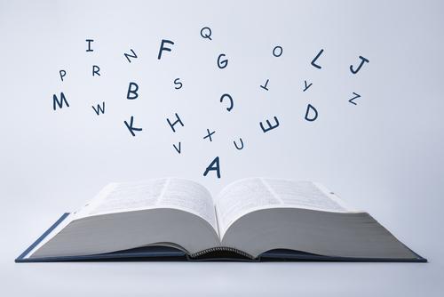 Ordbog med bogstaver flyvende ud af den
