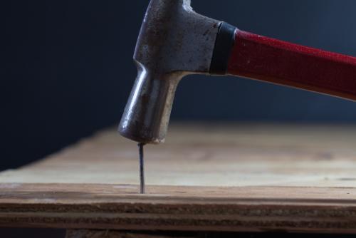 Hammer der slår et søm i et bræt