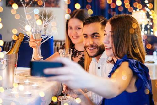 Unge festene tager selfie ved et festbord