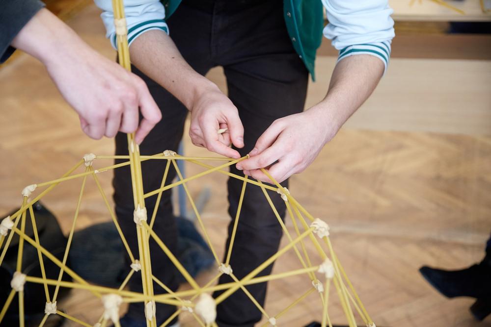 Folk bygger et tårn af spagetti