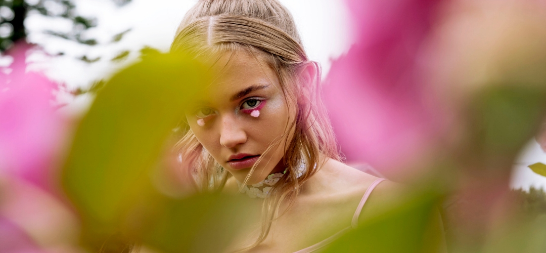 Fashion Photoshoot model looks through greenery at camera