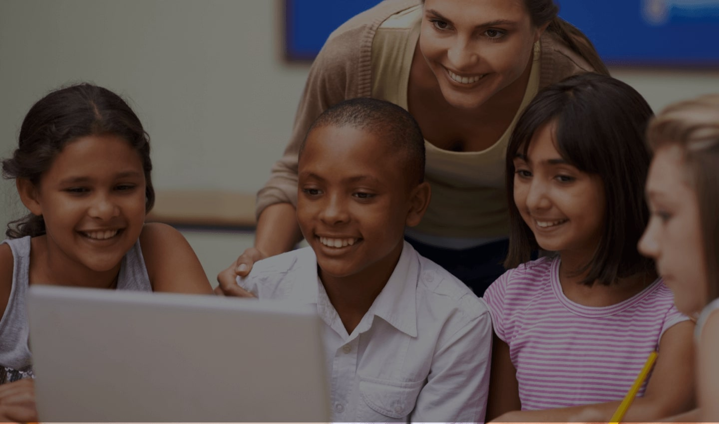 Smiling children with an women looking at laptop