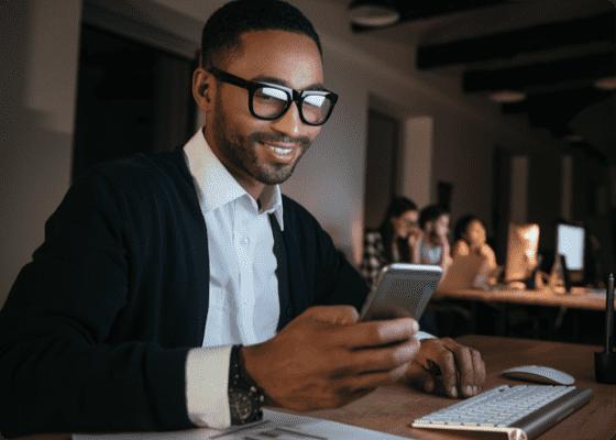 un hombre de traje mirando su celular con sonrisa
