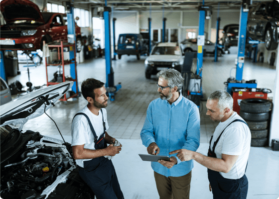 Un cliente hablando con los mecánicos en un taller