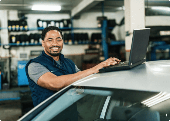 A car mechanic smiling with a laptop