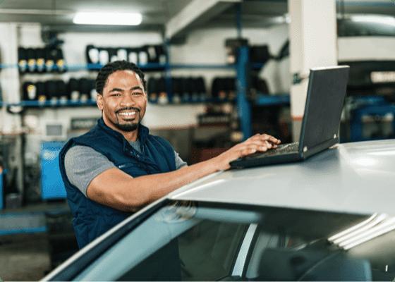 Un mecánico de coches sonriendo con un portátil