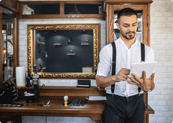 A barber smiling and checking his Setmore appointments on iPad
