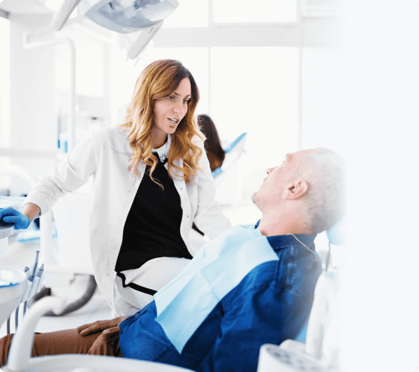 Dentist briefing her male patient on the treatment
