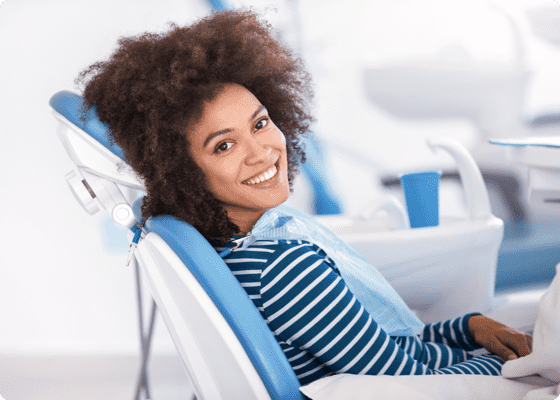 Curly haired smiling lady getting a dental check