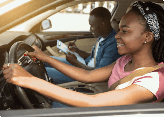 DMV instructor and young girl driving and smiling