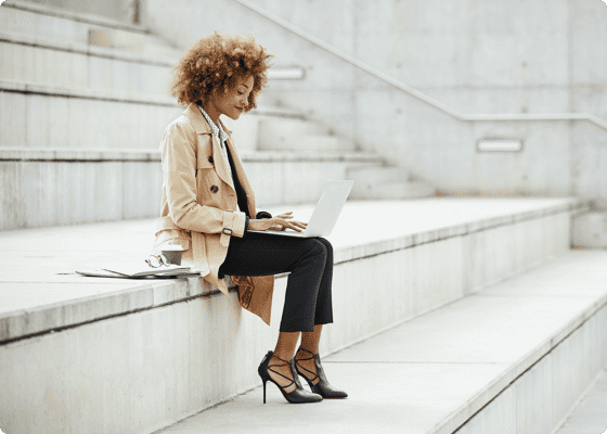 A woman sitting on stairs with a laptop