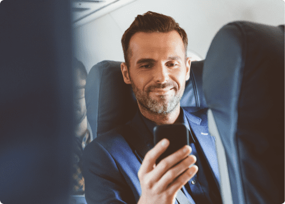 A man sitting in a plane with mobile