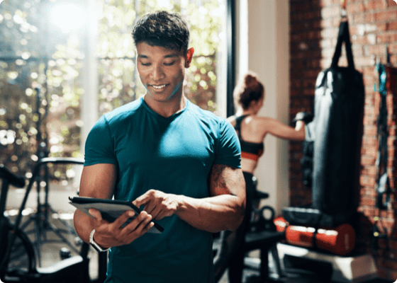 A smiling man tapping to his tablet in a gym