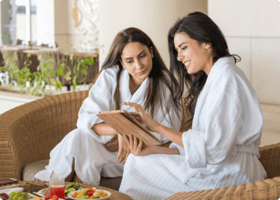 Two women sitting and discussing with a tablet