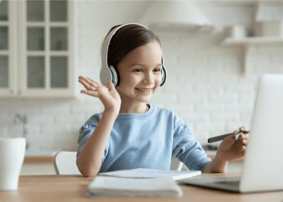 Smiling girl waving hand at Computer