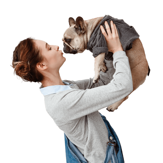 A lady carrying and kissing her dog